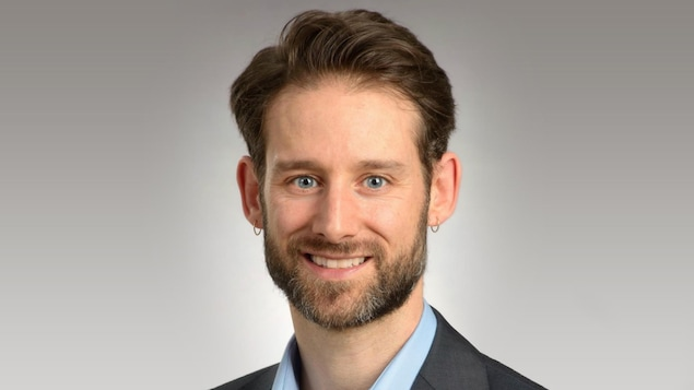 Un homme fin, dans la trentaine, en veston et chemise, avec un anneau à chaque oreille et une barbe courte, regarde en souriant l'objectif.