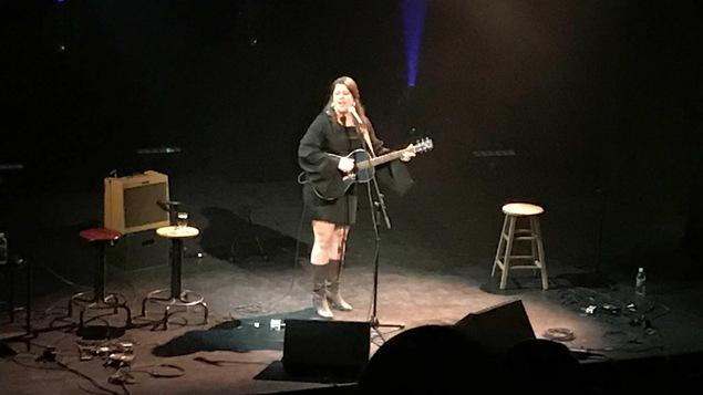 Andrina Turenne au micro avec sa guitare à la main.