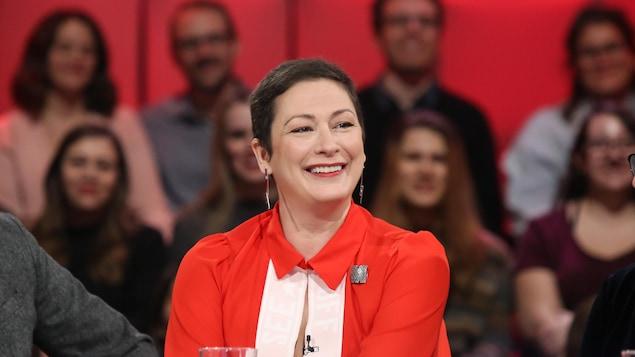 La femme vêtue de rouge sourit.