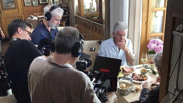Anthony Bourdain mange avec quelqu'un, entouré de caméramans.