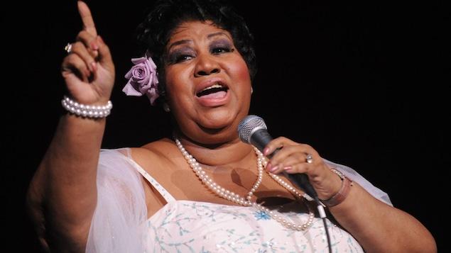 La chanteuse américaine Aretha Franklin tient un micro dans la main gauche et lève l'index de sa main droite.