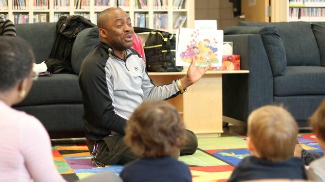 L'agent communautaire Arsène Mwamba entouré d'enfants auxquels il lit une histoire à l'Institut Guy-Lacombe pour la famille, à la Cite francophone d'Edmonton