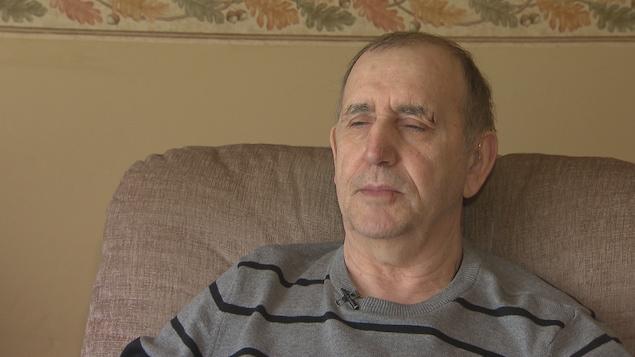 Réginald Arseneau assis dans un fauteuil, les yeux fermés