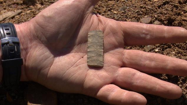 Pièce archéologique dans une main