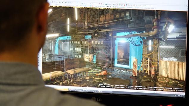 À l'aide du logiciel du moteur de jeu, Michel Lanoie manipule un objet dans un secteur du village Golem du jeu Deus Ex : Mankind Divided.