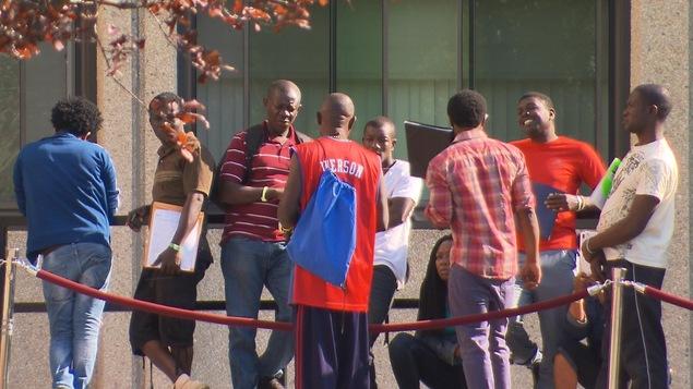Une dizaine de demandeurs d'asile font la file à l'extérieur pour obtenir leur chèque d'aide sociale à Montréal