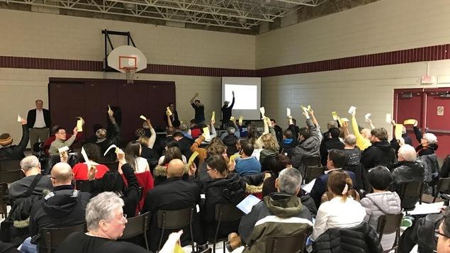 Des membres de l'Association des résidents du Vieux Saint-Boniface lèvent le bras pour voter.