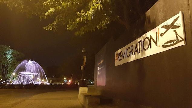 Une affiche « #remigration » à côté de la fontaine de Tourny