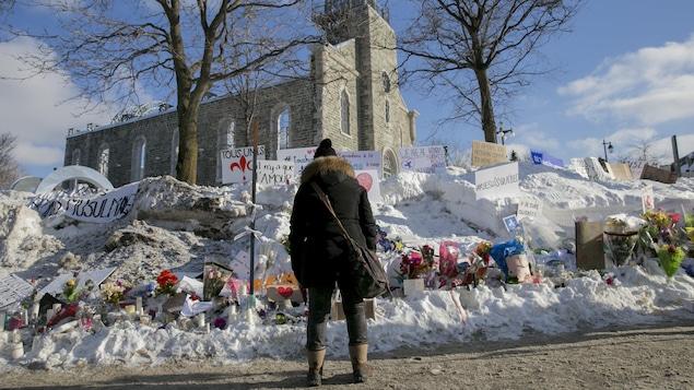 Une femme se recueille devant l'hommage aux victimes