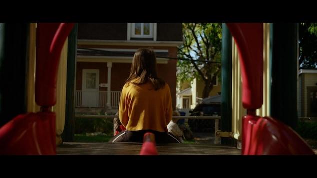 Un jeune est assis dans un module de jeu, de dos.