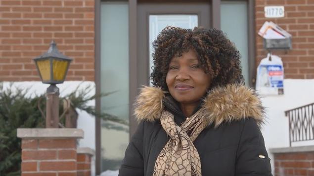 Augustine Deoua Gondgé devant chez elle, en manteau d'hiver et foulard