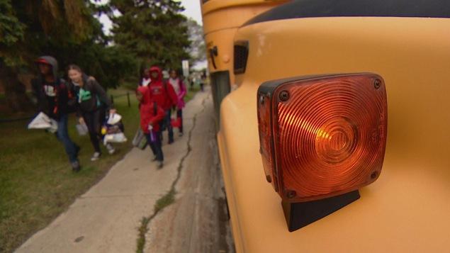 Gros plan sur une lumière d'un autobus scolaire. Des élèves floutés marchent à côté de l'autobus.