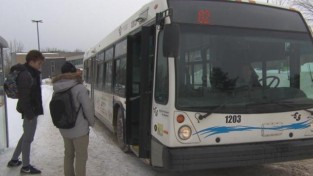 Un autobus de la STS avec deux étudiants qui attendent pour embarquer à l'intérieur.