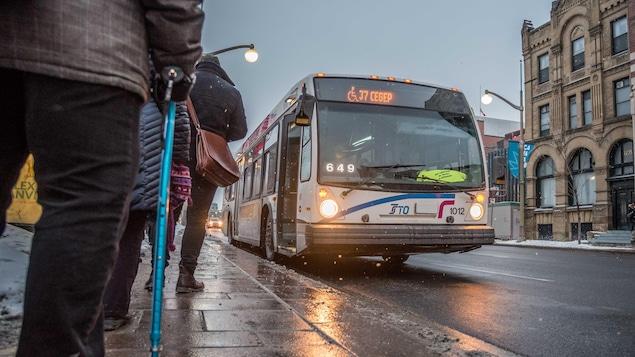 Des citoyens attendent un autobus de la Société de transport de l'Outaouais