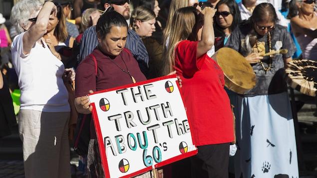 Des autochtones enlevés à leur famille quand ils étaient enfants et des gens qui les appuient manifestent à Toronto en août.