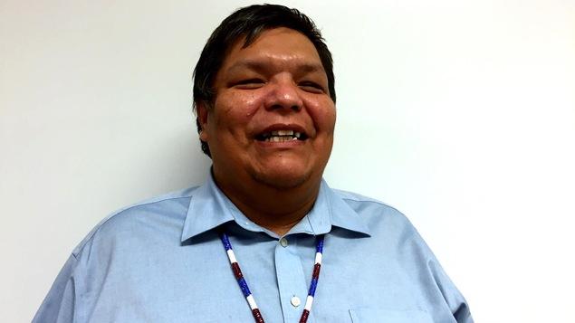Un homme est photographié de face, souriant.