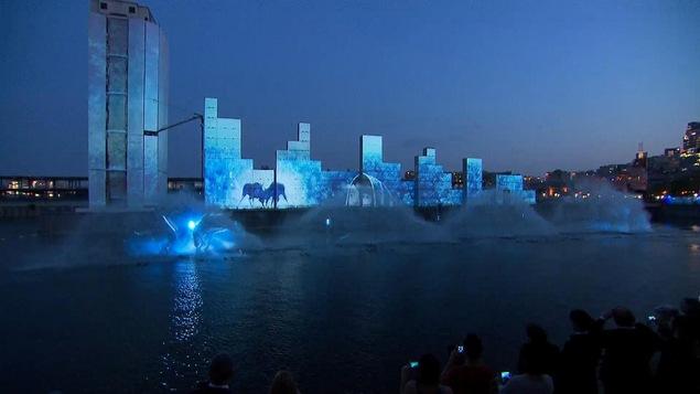 Des dessins bleus sont projetés sur des murs et des jets d'eau jaillissent devant ceux-ci.