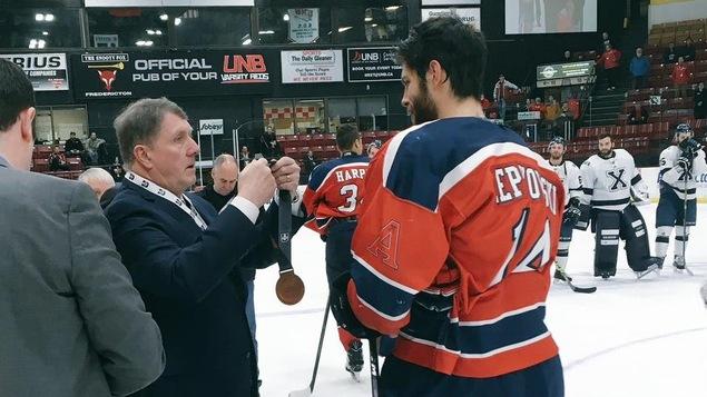 Un dignitaire accroche une médaille au cou d'un hockeyeur