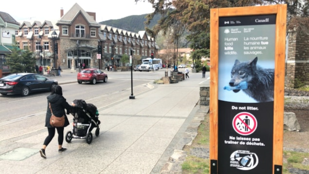 La publicité est affichée dans les rues de Banff, une femme passe à côté avec une poussette