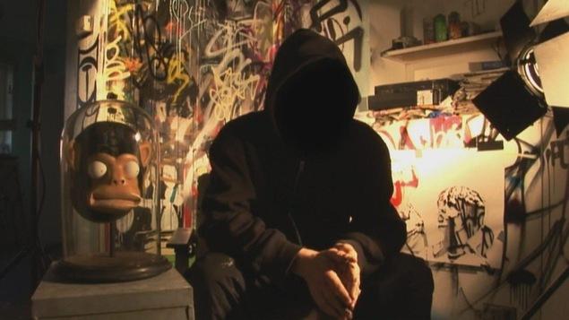 Un homme habillé en noir et cagoulé dont le visage est caché pose devant un mur de graffitis.