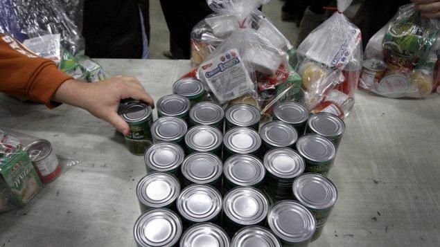 Boîtes de conserve dans une banque alimentaire, une main se sert une boîte