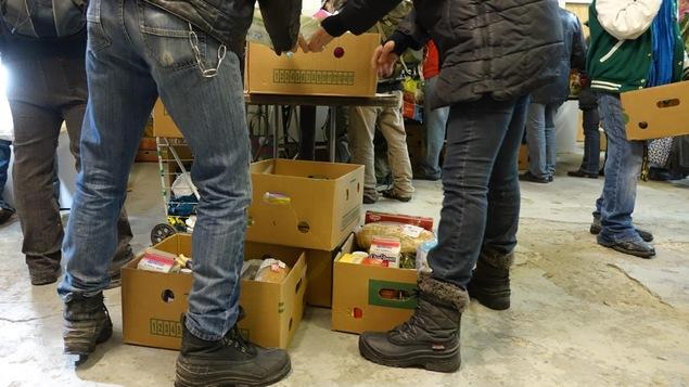 Des citoyens choisissent des denrées dans une banque alimentaire.