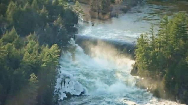 Un cours d'eau passe par dessus un barrage, entouré de forêt.