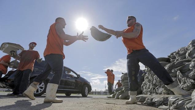 Des hommes chargent des sac de sable dans des voitures,