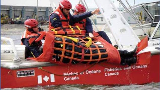 Des employés du ministère sur un petit bateau jettent à l'eau un radeau de sauvetage