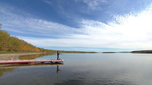 Un homme est sur un quai et pêche sur le Lac Beaver sous un ciel bleu.