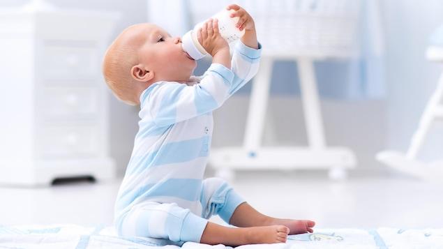 Un bambin boit goulûment à son biberon, vêtu d'un pyjama blanc et bleu