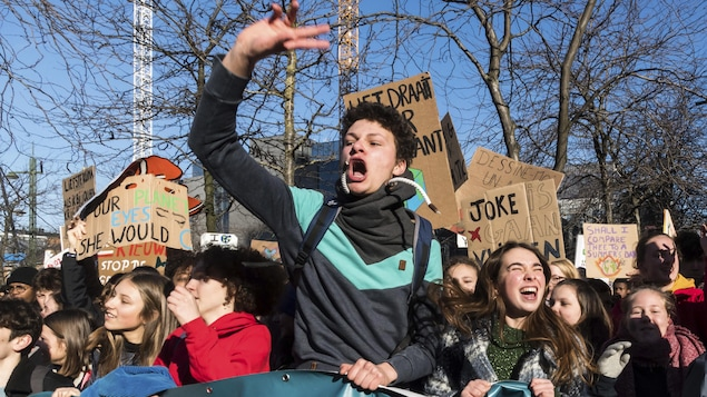 Un garçon crie avec la main levée entouré de ses amis brandissant des pancartes à la défense de la planète.