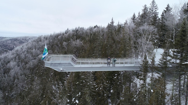 On voit un belvédère, en pleine nature, positionné au-dessus d'une falaise. Il est entouré d'arbres, de conifères principalement. C'est l'hiver, alors les branches des arbres sont parsemées de neige. Deux personnes se trouvent sur le belvédère. Au bout du belvédère, il y a un drapeau.