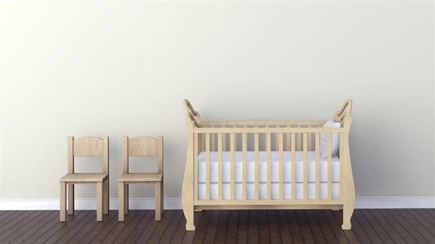 Un berceau et deux chaises posés dans une chambre