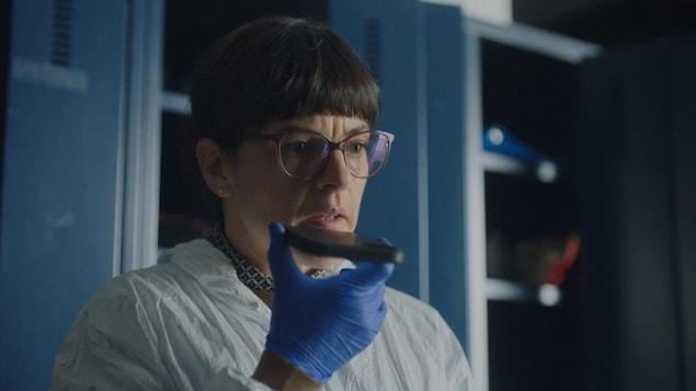 La femme, vêtue de gants bleus et d'une combinaison blanche pour éviter de contaminer une scène de crime, enregistre des notes vocales à l'aide d'un téléphone intelligent.