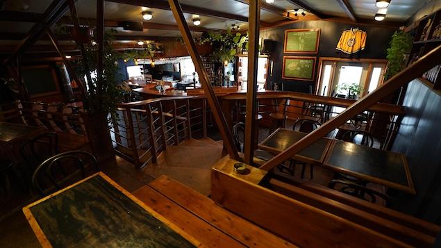 La salle de dégustation de la microbrasserie À l'abri de la tempête aux Îles-de-la-Madeleine avec des tables et le bar.