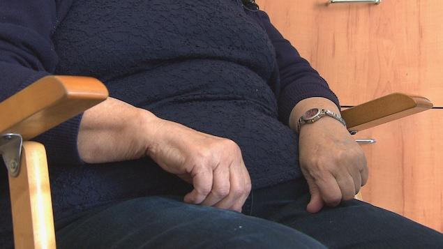 Les mains d'une femme posées sur ses cuisses en position assise.