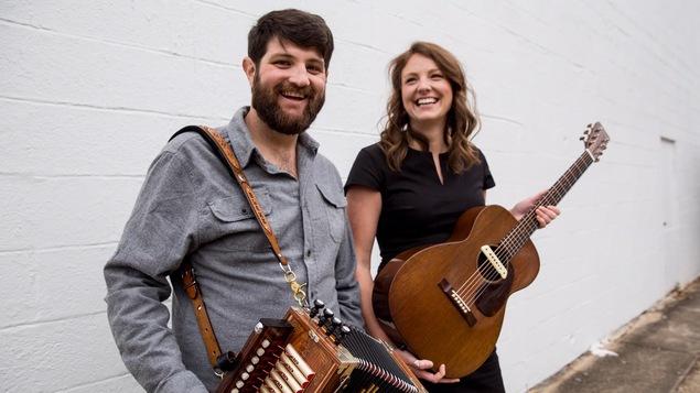Un homme avec un accordéon et une femme tenant une guitare rient dans une ruelle devant un mur de briques blanc.
