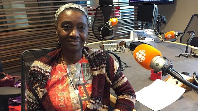 Une femme souriante portant un foulard sur sa tête est assise dans un studio de radio. À sa gauche, il y a un micro.