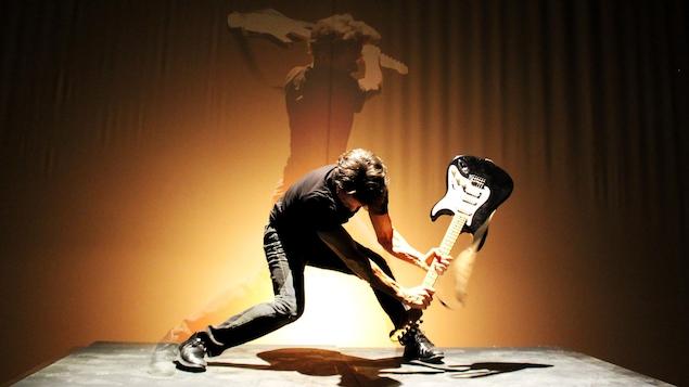 Un homme s'apprête à frapper une guitare sur le plancher d'une scène.