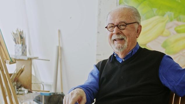 Un monsieur aux cheveux gris qui porte des lunettes rondes assis dans un studio de peinture.