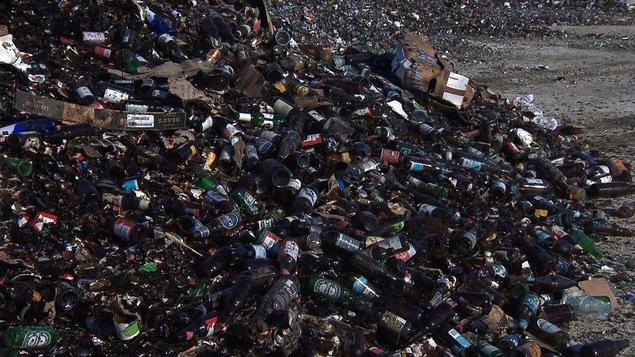 Une montagne de bouteilles vides dans un terrain vague.