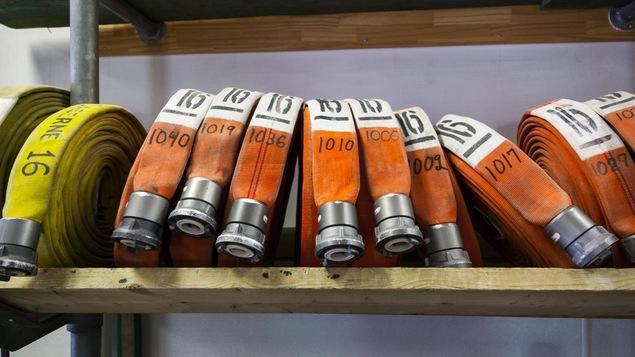 Des boyaux sont enroulés et entreposés pour une éventuelle intervention dans une caserne de pompiers de Montréal.