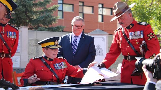 Branda Lucki signe un document sous l'oeil de Ralph Goodale et d'agents de la GRC en uniformes rouges.