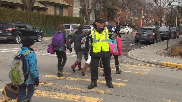 Un brigadier faisant traverser des enfants.