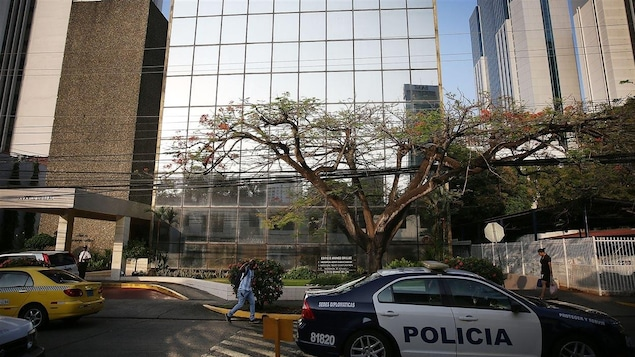 Une voiture de police est stationnée devant l'immeuble.