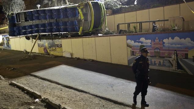Un autocar est couché sur le côté avec son toit arraché par les secours après un grave accident sur la colline de San Cristobal, près de Lima.