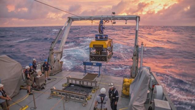 L'équipage d'un bateau s'apprête à mettre à l'eau un robot de recherche.