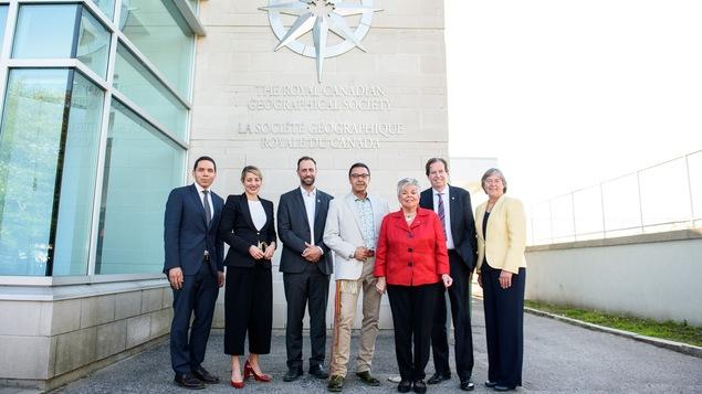Quatre hommes et trois femmes, tous vêtus d'un veston et d'une blouse, sont devant un logo argent près duquel on peut lire « Société géographique royale du Canada » et ils regardent la caméra en souriant.