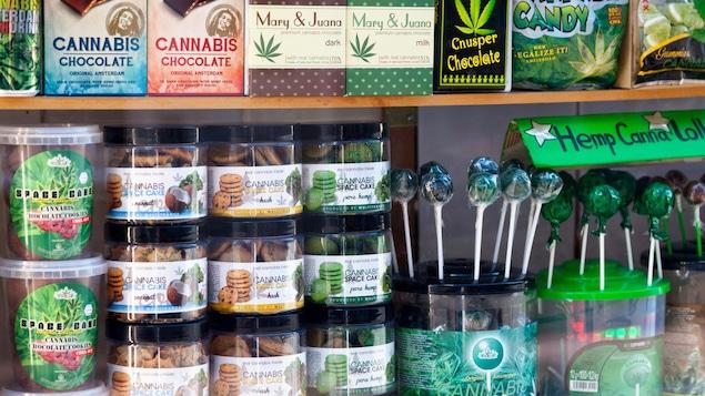 Plusieurs produits comestibles à base de cannabis sont présentés dans la vitrine d'un commerce.